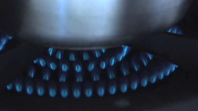 A gas burner heats a pot.