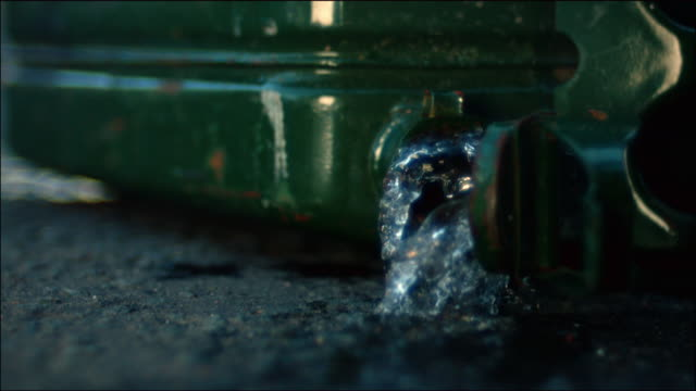 vídeos de stock e filmes b-roll de a gas canister falls and pours liquid; a match drops into a puddle of accelerant which quickly ignites - petroleum