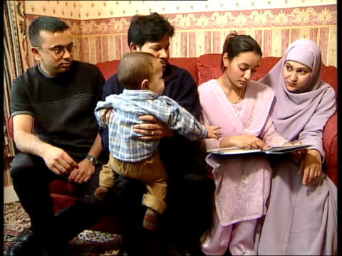 doctor allowed to continue working england london family of najiyah hussain sat on sofa relatives looking at photo album mohammed miah interview sot... - najiyah hussain stock videos and b-roll footage