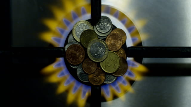 Gas Economy Concept and Coins on a Burning Stove as Energy Money Savings Top View Shot on Red