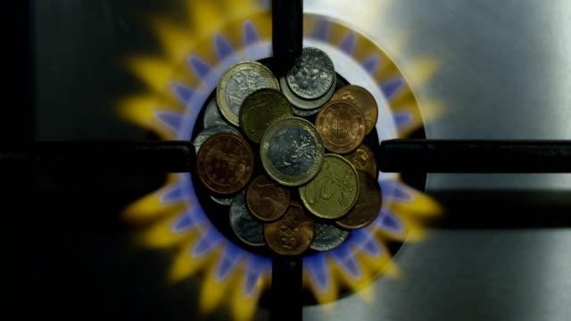vídeos de stock e filmes b-roll de gas economy concept and coins on a burning stove as energy money savings top view shot on red - european union coin