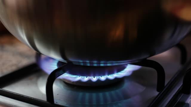 gas flame burning under a pot - cooker stock-videos und b-roll-filmmaterial