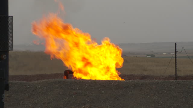 A gas flare burns near an oil well pump jack in North Dakota.