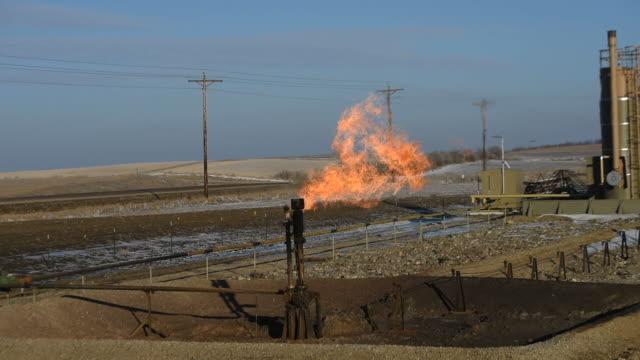 vídeos de stock, filmes e b-roll de gas flares burn excess natural gas from an oil well in bakken north dakota us on february 12 wide shot and close ups of gas flares burning from an... - poço de petróleo