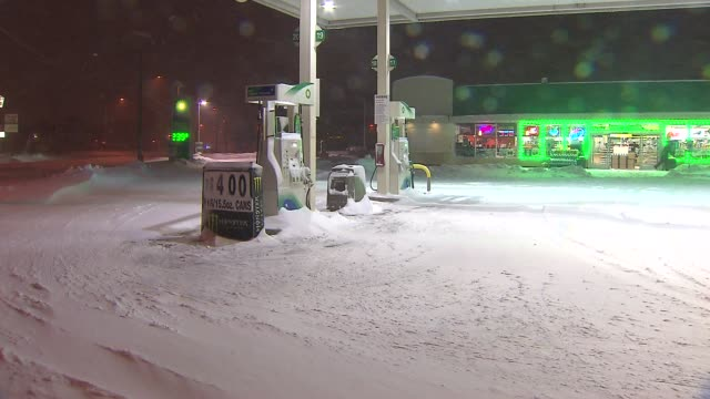 gas station and gas pump covered in snow during the 5th largest blizzard in chicago history on february 02 2015 in chicago illinois - ガソリンスタンド点の映像素材/bロール