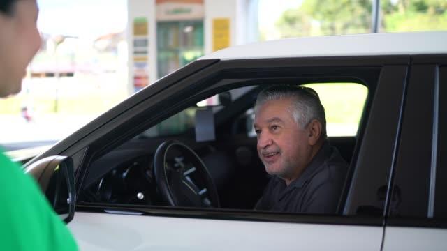 vidéos et rushes de préposé de station d'essence parlant au client à la voiture à la station-service - essence