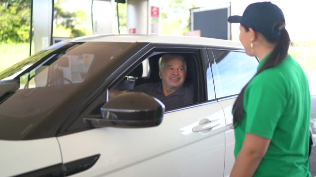 vídeos de stock e filmes b-roll de gas station attendant talking to customer at car at service station - frentista