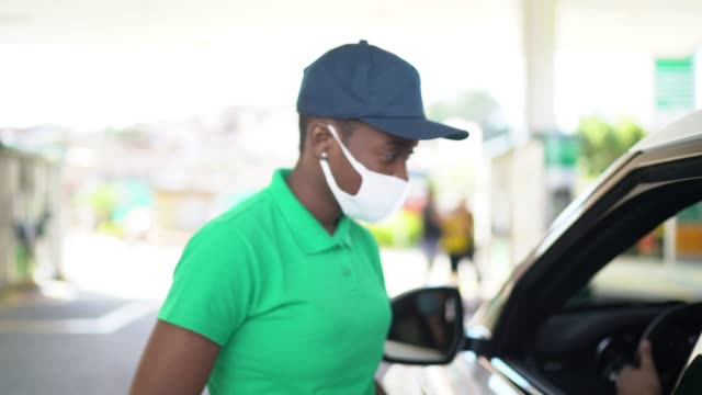 vídeos de stock e filmes b-roll de gas station attendant talking to customer at car at service station - with face mask - posto de gasolina