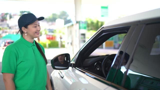 gas station attendant talking to customer at car at service station - stereotypical stock videos & royalty-free footage