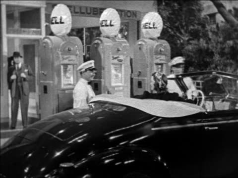 stockvideo's en b-roll-footage met b/w 1939 gas station attendant tipping hat to woman in convertible / shell oil gas pumps in background - kleine groep dingen