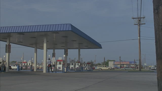 a gas station attendant waits around the pumps of his station in texas. - gas station attendant stock videos and b-roll footage