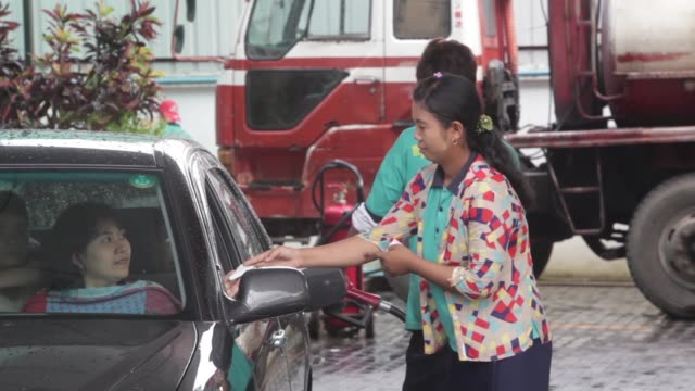 gas station attendants refuel cars at an mmtm gas station in yangon a gas station attendant refuels a motorist car as another hands over a bill at an... - gas station attendant stock videos and b-roll footage
