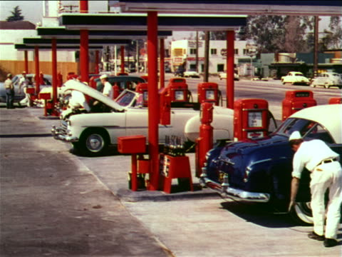 1951 gas station attendants servicing cars by gas pumps in gas station / industrial - gas station attendant stock videos and b-roll footage