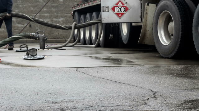 Gas station. Fuel truck driver pumping gasoline.