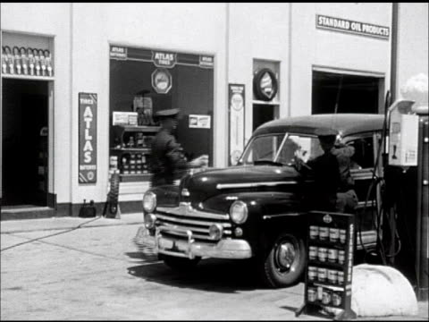service station xws gas station w/ four pumps freestanding 'standard' sign two uniformed attendants cleaning windshield of 1946 ford sedan car ms... - gas station attendant stock videos and b-roll footage
