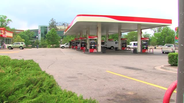 gas stations and people filling up their cars in denver, colorado, in the summer summer gas prices at shammrock gas station on june 12, 2012 in... - ガス料金点の映像素材/bロール