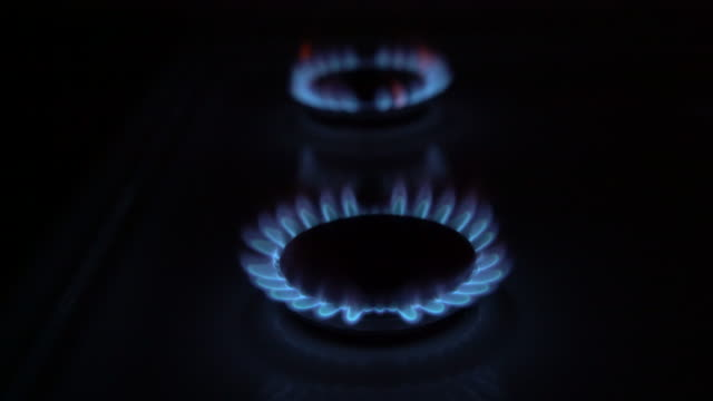 cu gas stove burner rings igniting into flames - ガスコンロ点の映像素材/bロール