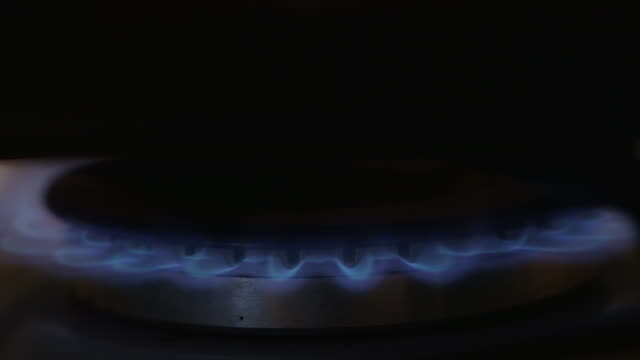 A gas stove is lit and and a saucepan placed on it, before the stove is turned off, UK.