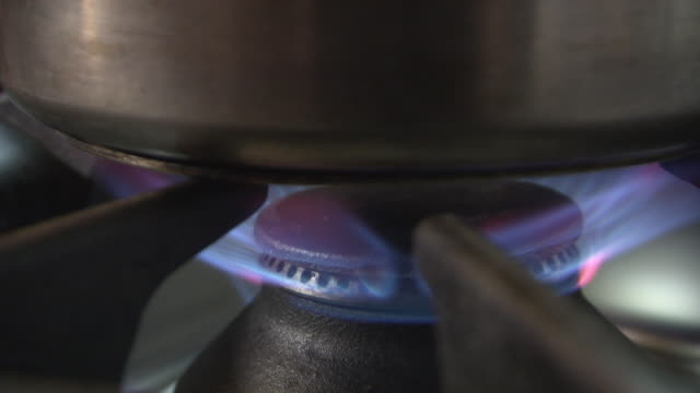 gas stove turned on under a saucepan - garkochen stock-videos und b-roll-filmmaterial