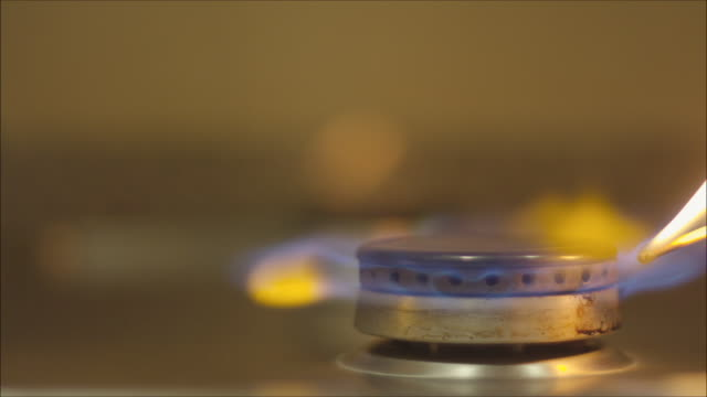 Gas stove turned on using a match. Close up. Nice blue flame. Ready to cook.