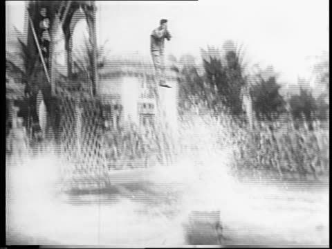 gasoline fueled fire burns on a swimming pool as soldiers jump into the water as part of the army air force's water safety training / from tower,... - swimming trunks stock videos & royalty-free footage