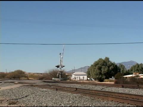 vídeos de stock e filmes b-roll de gate lowering at railroad crossing - baixar