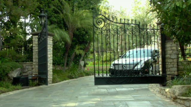 ms, gate opening, car driving through, gate closing behind it, beverly hills, california, usa - beverly hills stock-videos und b-roll-filmmaterial