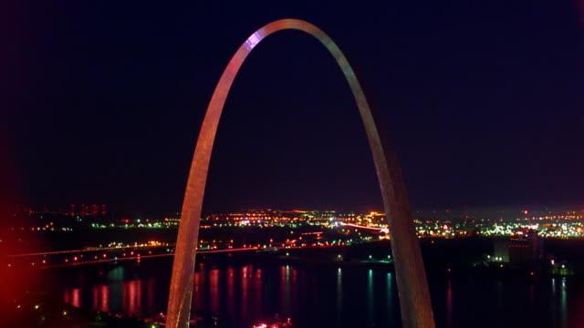 vídeos de stock e filmes b-roll de gateway arch at night with time lapse traffic and mississippi river in background / st. louis, missouri - arco gateway