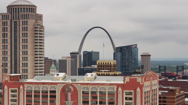 stockvideo's en b-roll-footage met gateway arch between st louis office buildings - drone shot - gateway arch st. louis