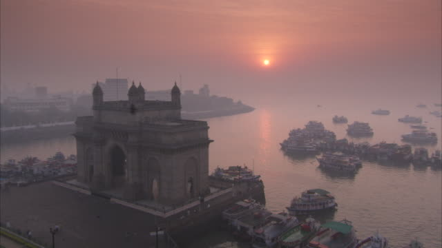Gateway of India with numerous ferries and boats moored around it at sunrise. Available in HD.