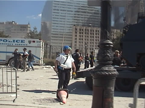 gather on north end ave, police dog handlers covered in dust leave the scene, a logistics coordinator arranges delivery of a police emergency rescue... - september 11 2001 attacks stock videos & royalty-free footage