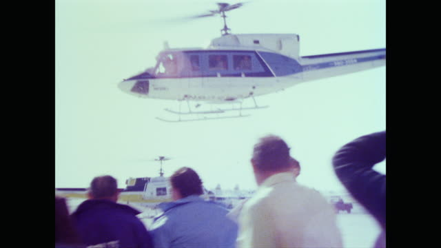 vídeos de stock e filmes b-roll de gathered crowd of press and visitors watch as prince charles's helicopter leaves the runway at edwards air force base - 1977