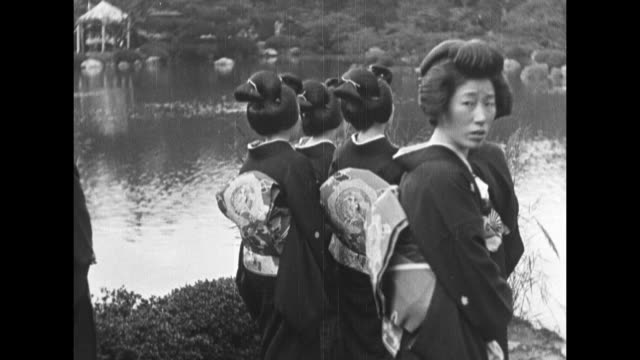gathering of men wearing suits and hats can see a geisha amid men tents in bg among trees / geishas dancing / geishas in fg looking across water one... - 1920年点の映像素材/bロール