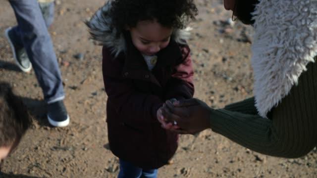 vídeos y material grabado en eventos de stock de recogiendo piedras en la playa - giving