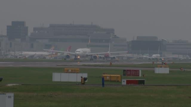 london gatwick airport vueling plane along on runway / various planes taking off / british airways plane along / norweigan airlines plane along /... - ライアンエアー点の映像素材/bロール
