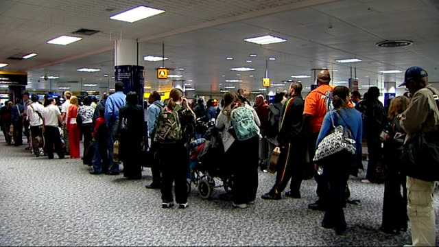 gatwick airport int people queueing at passport control point / passport control officer checking passports at desk / immigration officrs with... - control bildbanksvideor och videomaterial från bakom kulisserna