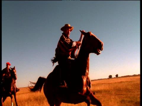 Gauchos riding on horseback, swinging boleadora, Argentina