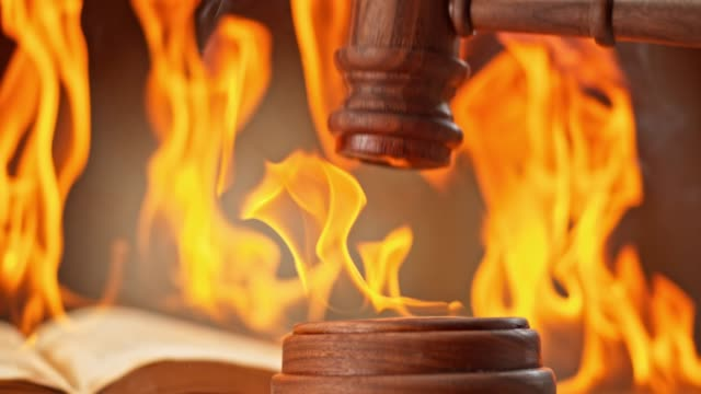 slo mo ld gavel striking a burning sound block on the desk with a book burning in the background - auction stock videos and b-roll footage