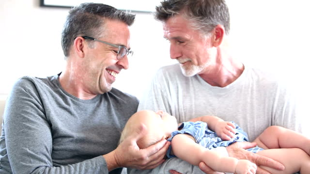 gay couple and a baby - cinquantenne video stock e b–roll