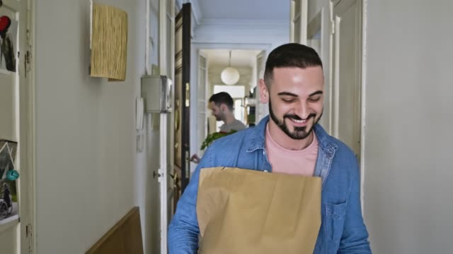 gay couple arriving back home with some shopping - paper bag stock videos & royalty-free footage
