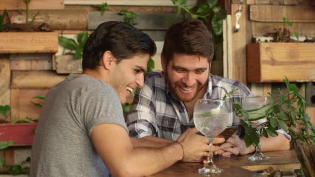 A gay couple chat and look at a mobile phone in a bar / Medellin, Colombia