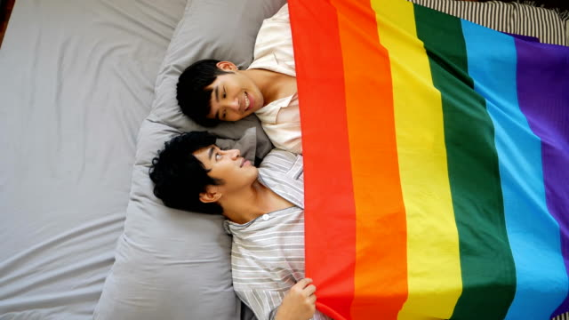 vidéos et rushes de couple gay couvre avec l'indicateur lgbt dormant sur la chambre à coucher - trans