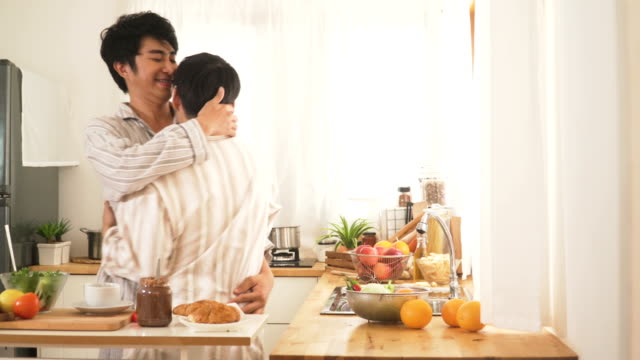 gay couple dancing and embracing in the modern kitchen after they wake up in morning