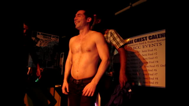 gay couple dancing together on the stage, one takes the shirt off of the other; the audience claps and cheers - other stock videos & royalty-free footage