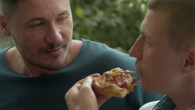 vídeos de stock e filmes b-roll de gay couple eating pizza - dividir
