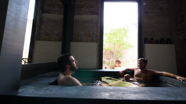 PAN Gay couple enjoying bath in spa at boutique hotel