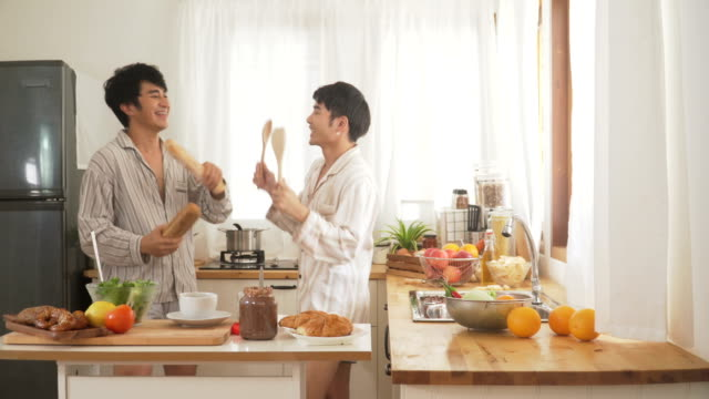 gay couple have fun dancing in the modern kitchen after they wake up in morning