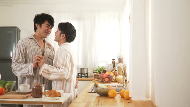 gay couple have romance dancing in the modern kitchen after they wake up in morning