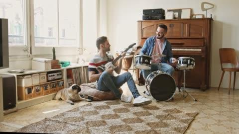 gay par ha roligt att spela musik hemma - musikinstrument bildbanksvideor och videomaterial från bakom kulisserna