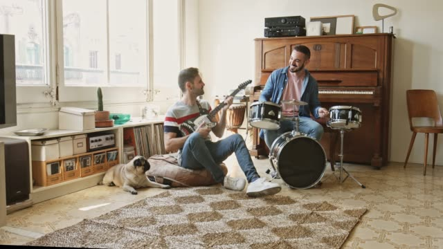 gay couple having fun playing music at home - drummer stock videos & royalty-free footage